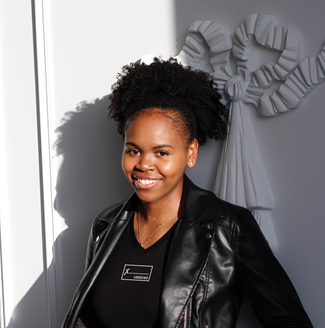 Dymika, a Black woman with her natural hair worn in a high ponytail and wears a cool leather jacket, smiles at the camera in front of a white wall.