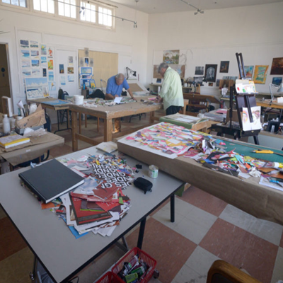 Image of 2 people painting in an artist studio, with painting supplies on numerous tables.