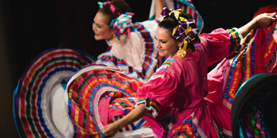 Colourful photo of 2 smiling dancers with their arms spread wide.