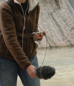 A person wearing a brown hoodie sweater and dark blue jeans holds a mic over an outdoor body of water to record the sound of the water..