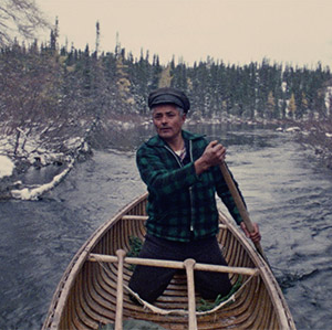 Caroline Monnet, Mobilize, 2015. A man kneels in a canoe and looks ahead as he paddles through an icy river.