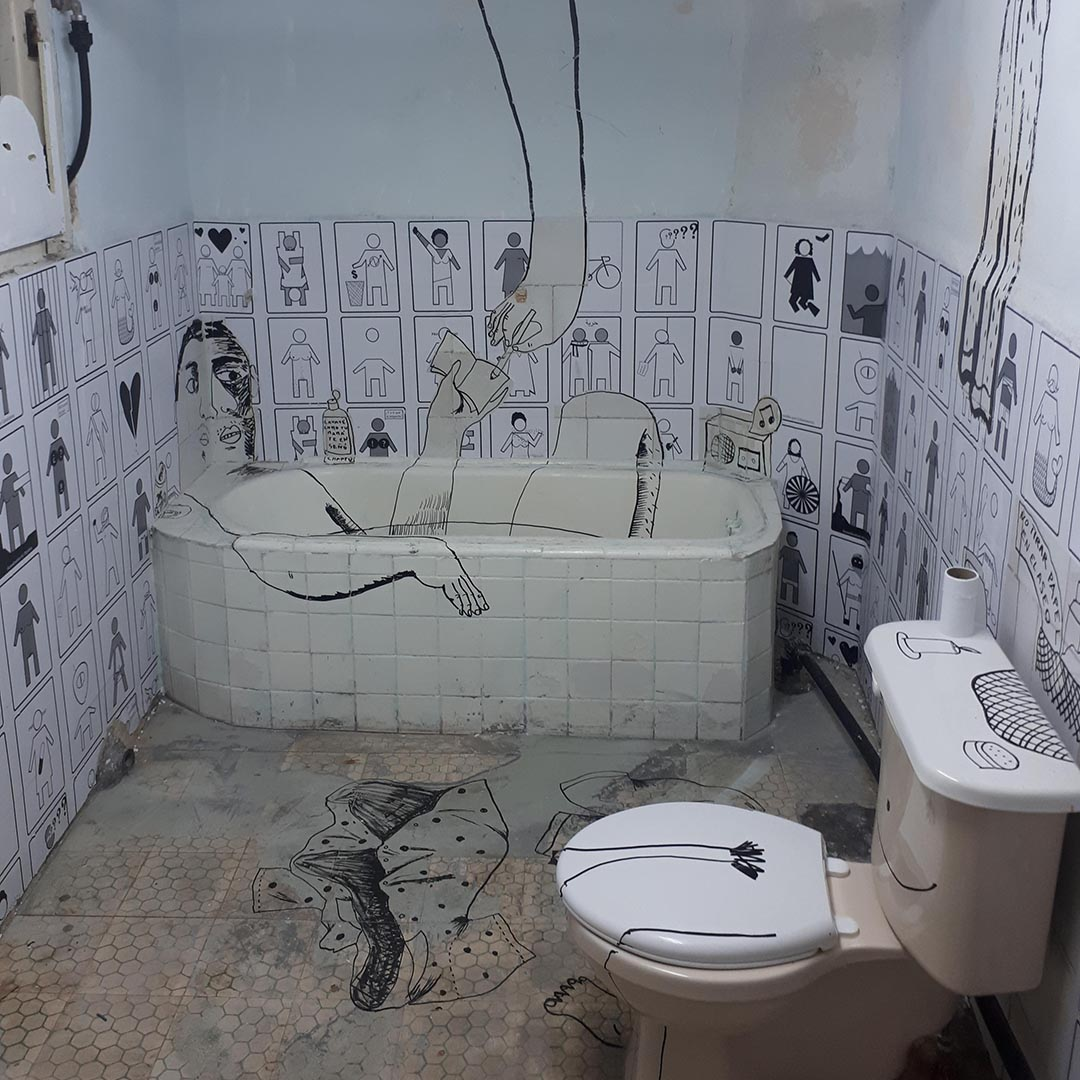 Photo of an old bathroom Coco has illustrated over in black market. There is a cartoon person lying in the bathtub.